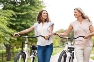 Two women holding bicycles after talking to their women's health care provider about aerobic exercise after menopause