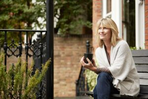 middle aged woman sitting on porch drinking coffee smiling after talking to a women's health care provider about her health