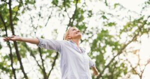 woman smiling with arms open because HRT helped boost her mood during menopause