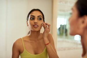 woman applying skin products to her face