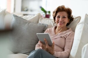 mature woman sitting on couch with iPad looking at strategies for lowering cholesterol after menopause