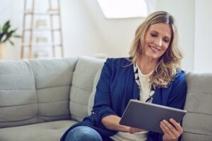 woman looking at tablet smiling while reading about laser aesthetic treatments for wrinkles and fine lines