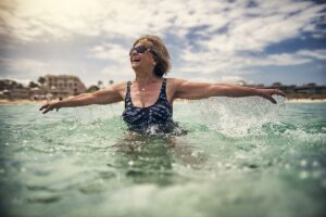woman swimming and smiling after estrogen replacement therapy helped relieve menopause symptoms