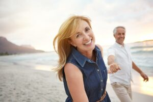 woman in perimenopause holding hands on the beach with a man